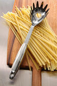 Fettuccine on wooden cutting board — Stock Photo