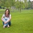 Woman sitting on a green grass — Stock fotografie