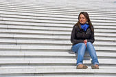 Woman sitting on the marble steps squinting in the sunlight — Stock Photo