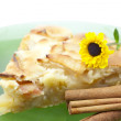 Apple pie, a flower on a plate and cinnamon - Stock Photo