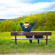 Male resting on the bench on the field of dandelions — Stock Photo