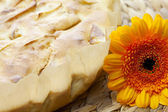 Apple pie and a flower on a wicker mat — Stock Photo