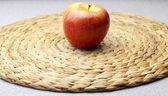Apple on a wicker mat — Stock Photo