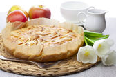 Apple pie, tulips, apples and glassware on a wicker mat — Stock Photo