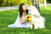 Young bride and the dog on the nature — Stock Photo