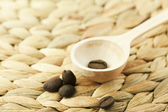 Wooden spoon and coffee beans are on the wicker material — Stock Photo