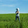 Young man covering the face paper in green field — Stock Photo