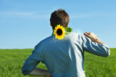 Young man standing with a sunflower in the green field — Stock Photo
