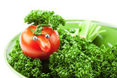 Tomato with a nose on the plate and the green isolated on white — Stock Photo