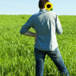 A young man and a sunflower field - Stock Photo