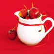Milk jug ribbon  cherry and strawberry on a red background — Photo