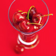 Glass of cherry  on a red background — Zdjęcie stockowe