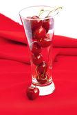 Vidrio de cereza sobre un fondo rojo — Foto de Stock
