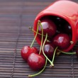 Cherry  and cup  on bamboo mat - Stock Photo