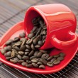 Stock Photo: Cup and saucer and coffee beans on bamboo mat