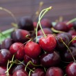 Cherry in plate on a bamboo mat — Stock Photo