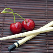 Cherry and chopsticks on bamboo mat - Stock Photo