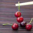 Cherry and chopsticks on bamboo mat — Stock Photo