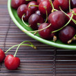 Cherry in plate on a bamboo mat - Stock Photo