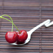 Cherry in spoon on a bamboo mat - Stock Photo