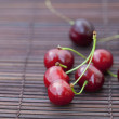 Cherry  on bamboo mat — Stock Photo