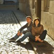 Love couple sitting on the pavement — Stock Photo #5996573
