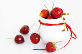 Milk jug ribbon cherry and strawberry isolated on white — Stock Photo