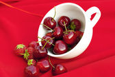Cherries and strawberries in a white cup on a red background — Stock Photo