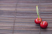 Two cherries in plate on a bamboo mat — Stockfoto