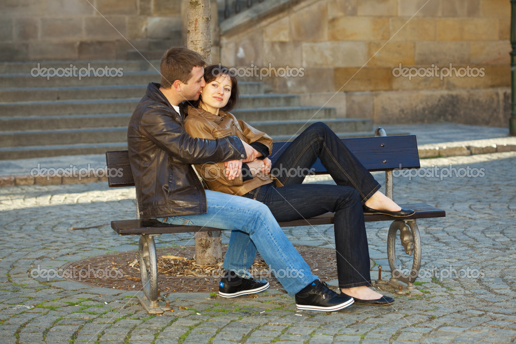 Love couple sitting on the bench — Stock Photo #5996446