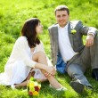 Just married in a flowering garden sitting on the grass — Stock Photo #6000174