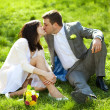 Just married in a flowering garden sitting on the grass — Stock Photo #6000188
