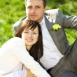 Just married in a flowering garden sitting on the grass — Stock Photo