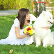 Bride with dog Samoyed sitting on the grass - Photo
