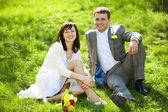 Net getrouwd in een bloeiende tuin zittend op het gras — Stockfoto