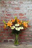 Flowers in a vase standing in the background of a brick wall — Stock Photo
