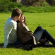 Young couple sitting on the green grass — Stock Photo
