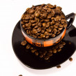 Cup and saucer with the coffee beans isolated on white — Stock Photo