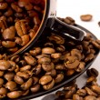 Stock Photo: Cup and saucer with the coffee beans isolated on white