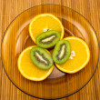 Kiwi fruit and oranges on a plate — Stock Photo