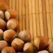 Hazelnuts isolated on a bamboo mat — Stock Photo