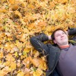 Portrait of a man lying on autumn leaves — Stock Photo
