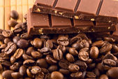 A bar of chocolate and coffee beans lying on a bamboo mat — Stock Photo