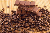 Chocolate and coffee beans on a bamboo mat — Stock Photo