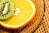 Apelsin och kiwi frukt på en tallrik — Stockfoto
