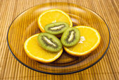Kiwi fruit and oranges on a plate — Stock fotografie