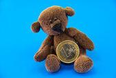 Teddy bear and euro coins — Stock Photo