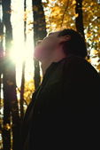 Man looking at the sun in the autumn forest — Stock Photo