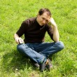Man sitting on green grass — Stock Photo