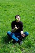 Muž sedící na zelené trávě — Stock fotografie